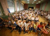 dzieci siedzące w auli szkolnej podczas rozpoczęcia roku szkolnego