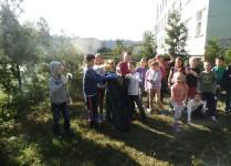 Grupa dzieci na boisku szkolnym wrzuca śmieci do worka