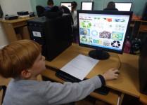 Chłopiec w pracowni komputerowej poznaje oznaczenia dotyczące recyclingu