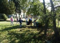 Dzieci z workami i rękawicami zbierają śmieci z terenu wokół szkoły