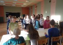 Grupa dzieci zebrana w auli szkolnej podczas głosowania