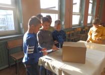Chłopcy wrzucający swoje głosy do urny wyborczej