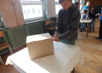 Chłopiec wrzucający głos do urny