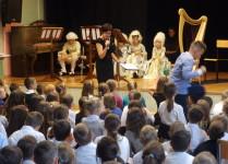 prowadząca koncert opowiada o epoce baroku w tle dzieci w strojach z epoki
