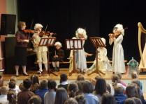 dzieci w strojach z epoki podczas gry na skrzypcach