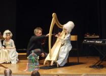dziewczynka w stroju z epoki baroku grająca na harfie