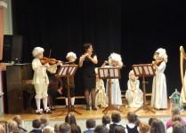 dzieci w strojach z epoki baroku wraz znauczycielką grają na skrzypcach i fletach poprzecznych