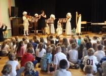dzieci słuchające koncertu w wykonaniu kolegów ze szkoły muzycznej