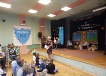 Pani Magdalena Szmidt wita brzybyłych uczniów, nauczycieli i pracowników szkoły w auli szkoły.