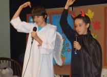 Chłopcy przebrani za anioła i diabła śpiewają piosenkę dla katechetów