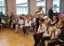 W auli szkoły siedzą dzieci w strojach galowych. Na zdjęciu widoczne dzieci z niebieskimi i bordowymi kokardami pod szyją.