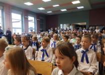 Dzieci z klas 1a i 1c siedzące w auli szkolnej