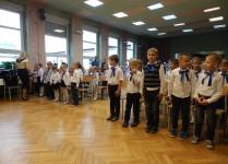 Dzieci z klasy 1a i 1b stojące w czasie wprowadzania sztandaru szkoły
