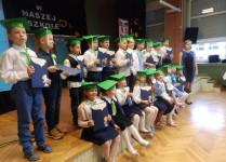 Dzieci z klasy 1c z wychowawcą pozują do grupowego zdjęcia na scenie w auli