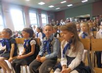 Dzieci z klasy 1d siedzące w auli szkolnej
