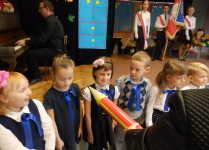 Sześioro dzieci stojących w rzędzie, Pani dyrektor ołówkiem pasuje jedną z dziewczynek na ucznia