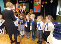 Dzieci z klasy 1d stoją w rzędzie i odbierają dyplomy pasowania