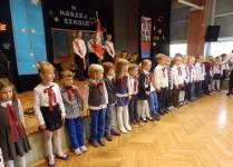 Dzieci z klasy 1e stojące w rzędzie w oczekiwaniu na pasowanie