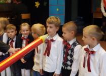 Siedmioro dzieci, chłopiec w środku włąśnie jest pasowany przez Panią dyrektor na ucznia