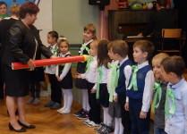 Dzieci z klasy 1f, chłopiec w środku właśnie jest pasowany na ucznia