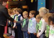 Grupa dzieci, jeden z chłopców ściska dłoń Pani dyrekto i przymuje gratulacje z okazji pasowania