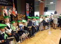Uczniowie klasy 1f w dzielonych biretach stoją przed sceną tuż po pasowaniu