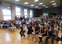 DZieci w granatowych, bordowych i zielonych biretach siedzą w auli szkoły po pasowaniu