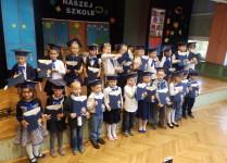 Dzieci z klasy 1d ustawione do zdjęcia grupowego na scenie w auli