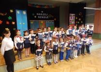 Uczniowie klasy 1e z wychowawcą ustawieni do zdjęcia grupowego w biretach i z dyplomami