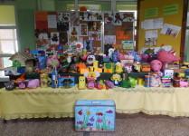 W holu szkoły stoją stoły, na których wyeksponowano przyniesione prace