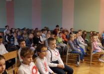 Dzieci siedzące w auli szkoły podczas obchodów Świeta NIepodległości