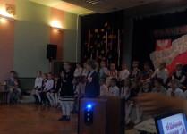 Przyciemnione światła, chłopiec i dziewczynka mówią wiersz, w tle siedzą dzieci z Muzykowa