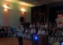 Przyciemnione światła, chłopiec prowadzący skotkanie, w tle siedzą dzieci z Muzykowa
