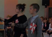 """Chłopiec i dziewczynka wyciągają ręce z mikrofonami w stonę widowni by wspólnie mówić wiersz """"Kto Ty jesteś"""""""