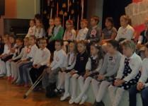 Dzieci z Muzykowa siedzą na scenie podczas występu