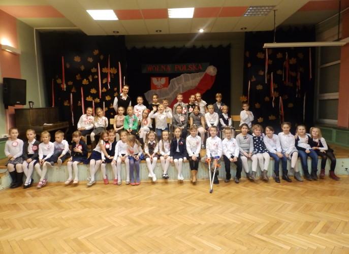 Dzieci z Muzykowa ustawione na scenie razem z opiekunką