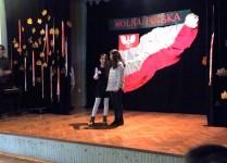 NA scenie dwie dziewczynki w strojach galowych śpiewają do mikrofonu, w tle flaga i godło Polski