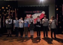 Grupa dzieci z klasy 5A, każda trzyma w ręce kartę z literą, które składają się na słowo listopad