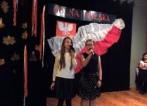 Dwie dziewczynki z klas szóstych na scenie, w tle flaga i godło Polski
