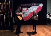 Solistka z akompaniatorem - na gitarze gra nauczyciel muzyki