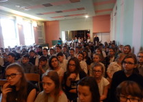 Dzieci z klas IV-VI, ubrani na galowo, siedzą w auli słuchając występów swoich koleżanek i kolegów