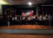 Na scenie wszyscy uczestnicy konkursu wraz z nauczycielem muzyki, w tle flaga i godło Polski