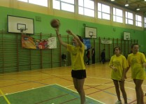 DZiewczynki w żółtych koszulkach trenują rzuty do kosza