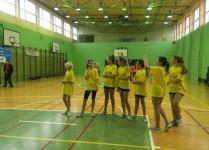 Dziewczynki stoją w rzędzie w sali gimnastycznej czekają na rzuty do kosza
