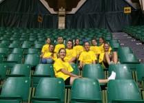 Nasze zawodniczki w żółtych koszulkach siedzą na trybunach przed zawodami