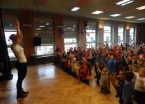 Nauczycielka na scenie w czapce Mikołaja klaszcze nad głową, ponożej dzieci tańczą razem z nią
