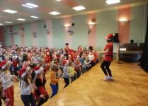Nauczycielka na scenie skacze w bok, poniżej dzieci naśladują choreografię