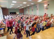 Dzieci w auli szkoły tańczą z wyciągniętymi do góry rękami