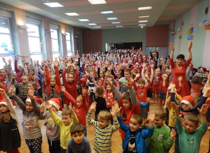 DZieci i nauczyciele podskakują w rtym muzyki z rękami uniesionymi do góry