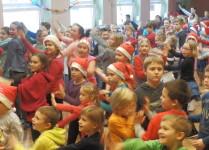 dzieci w czapkach Mikołaja tańczą w auli szkoły